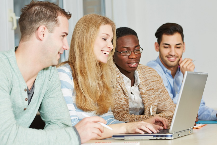 4 students looking at laptop