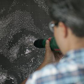 Artist using a hand-drill to pierce through paper