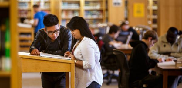 2 students standing in the library