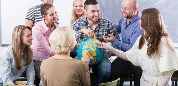 Group of students pointing to a globe