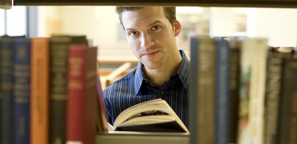 Faculty Center Student Peaking Through Book Isle Image