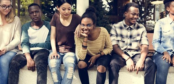 Group Of Students Sitting On A Wall