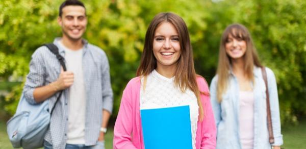 Three Students Standing Outside With Books