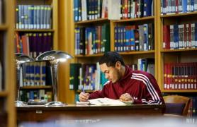 male student seated in library
