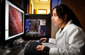 girl in white lab coat looking at PC