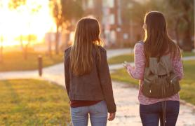 Two Students Walking In The Setting Sunlight