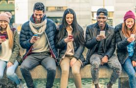 Students engaged with their smartphones on campus