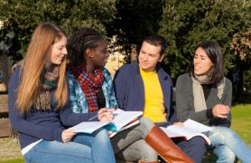 Students Outside Reading From Textbook